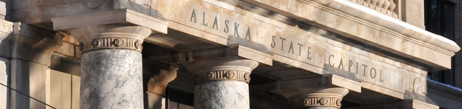 Detail view of the marble portico bearing the carved words Alaska State Capitol